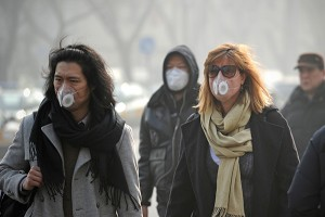 People wearing face masks walk along a street  in Beijing on January 16, 2014.  China's capital was shrouded in thick smog on January 16, cutting visibility down to a few hundred metres as a count of small particulate pollution reached more than 20 times recommended levels.        AFP PHOTO / WANG ZHAO